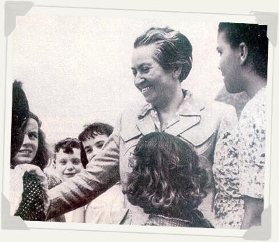 Gabriela sonriendole a varios niños que están junto a ella.
